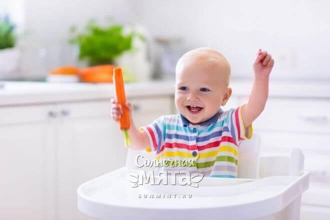 Маленький мальчик радостно держит в руках морковку, фото