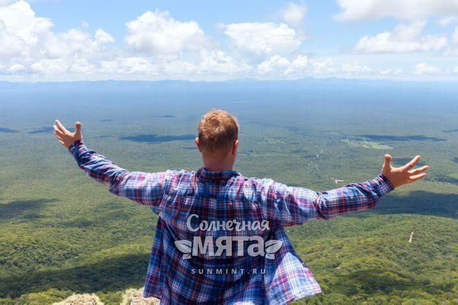 Молодой парень смотрит с холма вниз на долину, фото