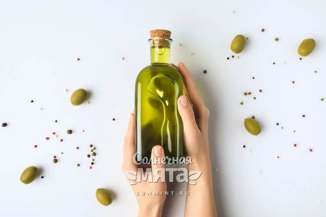 Девушка держит в руках бутылку с растительным маслом, фото