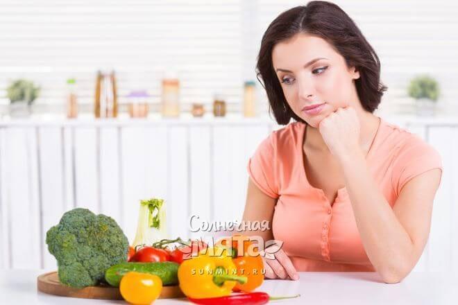 Женщина размышляет, глядя на овощи на своем столе, фото