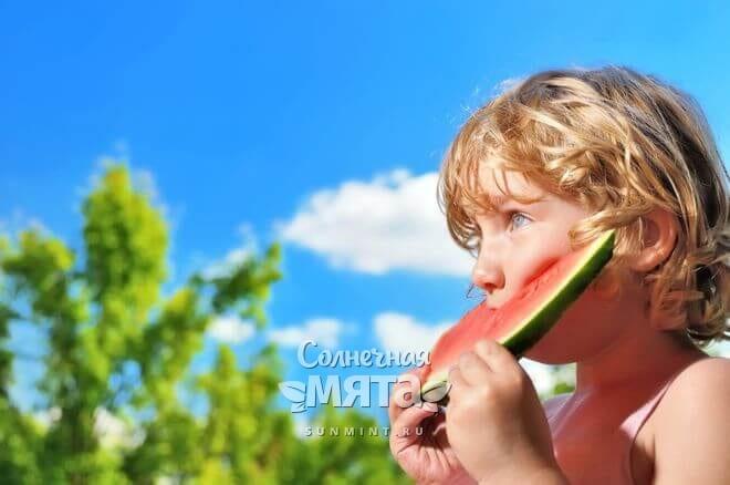 Мальчик ест арбуз на природе, фото