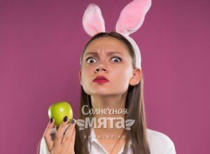 Смешная девушка с кроличьими ушами держит в руках яблоко, фото