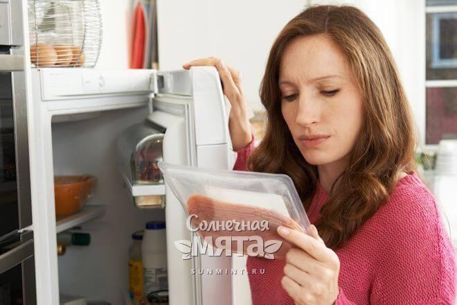 Женщина достает из холодильника пакет с мясом, фото