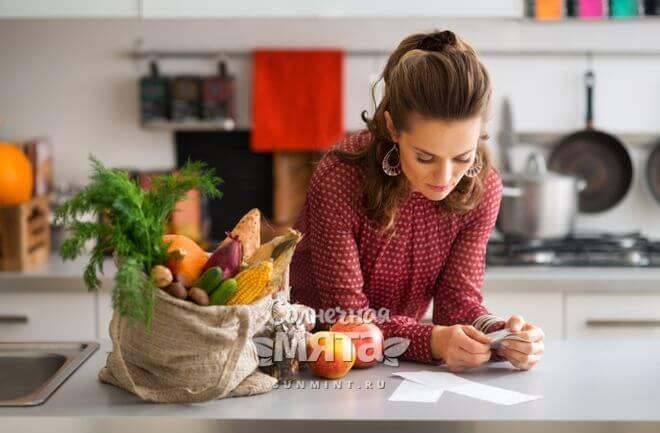 Женщина изучает кассовый чек после покупки продуктов, фото