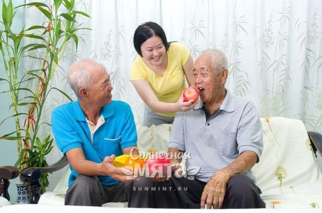 Внучка-китаянка угощает своего дедушку яблоком, фото